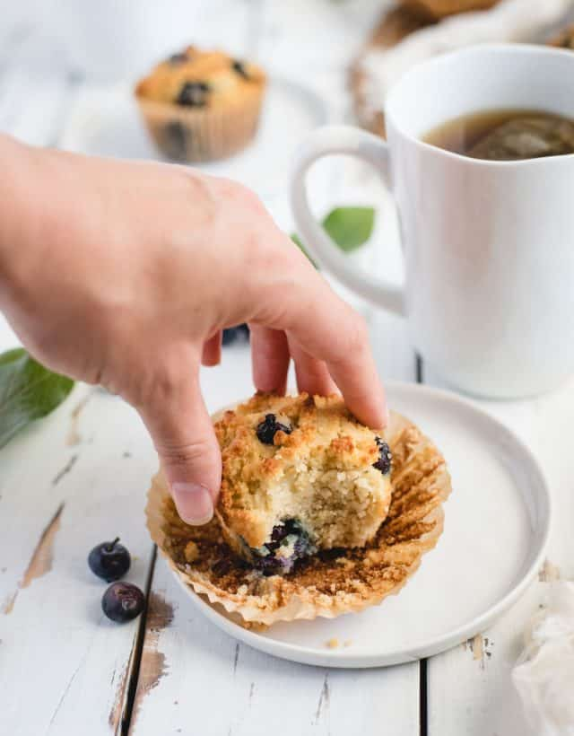 Hand reaching out to grab a gluten free blueberry muffin off of a plate