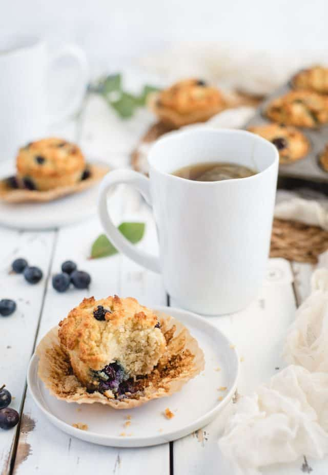 close up picture of a blueberry muffin on a white plate with a cup of tea