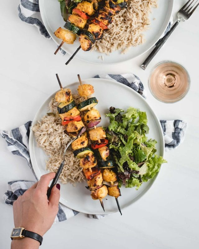 Hand cutting into a yogurt marinated chicken kabob on a plate on a white background