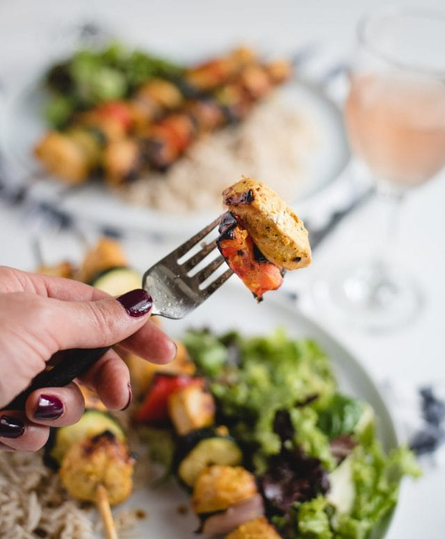 hand holding a bite of yogurt marinated chicken and red pepper up on a fork