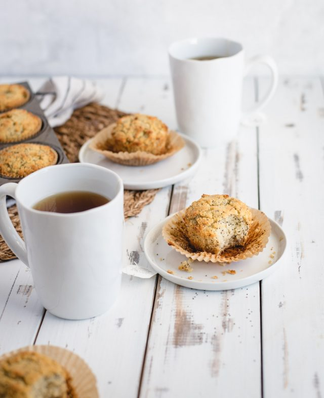 two plates with almond poppy seed muffins on a white table with cups of tea