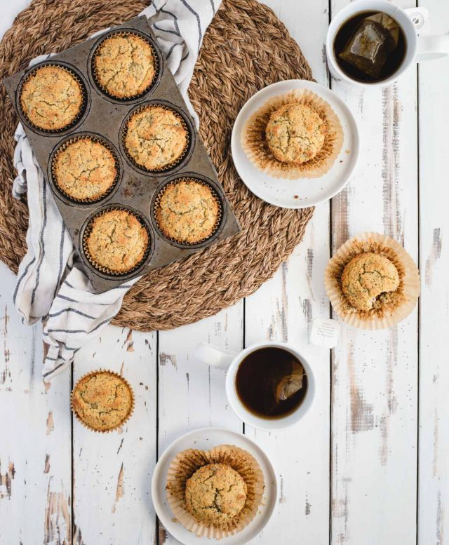overhead table scape picture of almond poppy seed muffins in a muffin tin next to two place settings with muffins on small plates and cups of tea