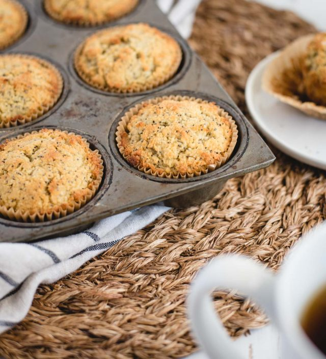close up picture of almond poppy seed muffins in a muffin tin