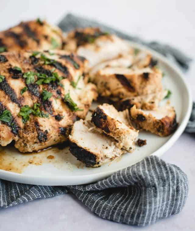sliced grilled chicken on a plate next to several whole breasts