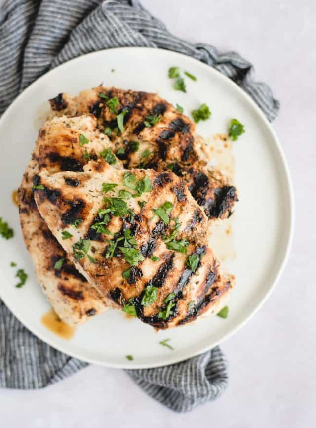 overhead picture of grilled chicken breasts on a white plate