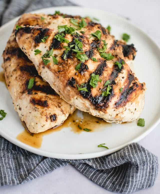 greek chicken breasts stacked on a plate
