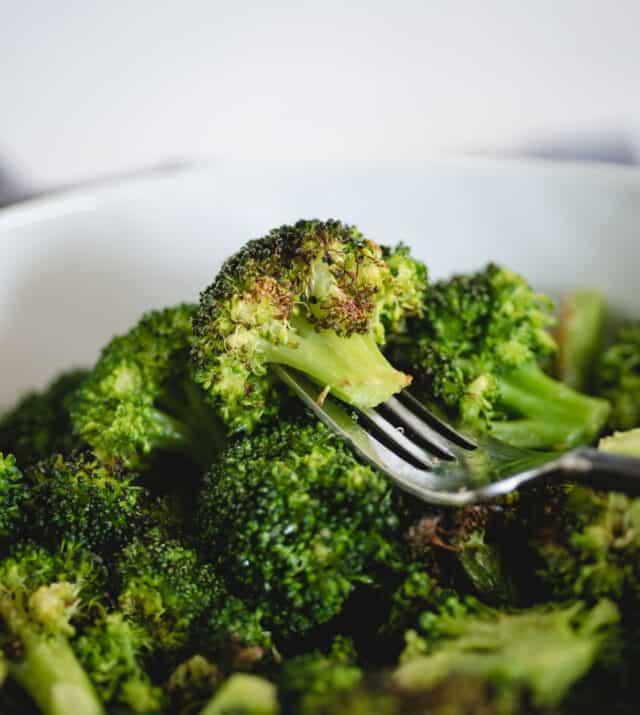 Broccoli on a fork inside a larger bowl of broccoli