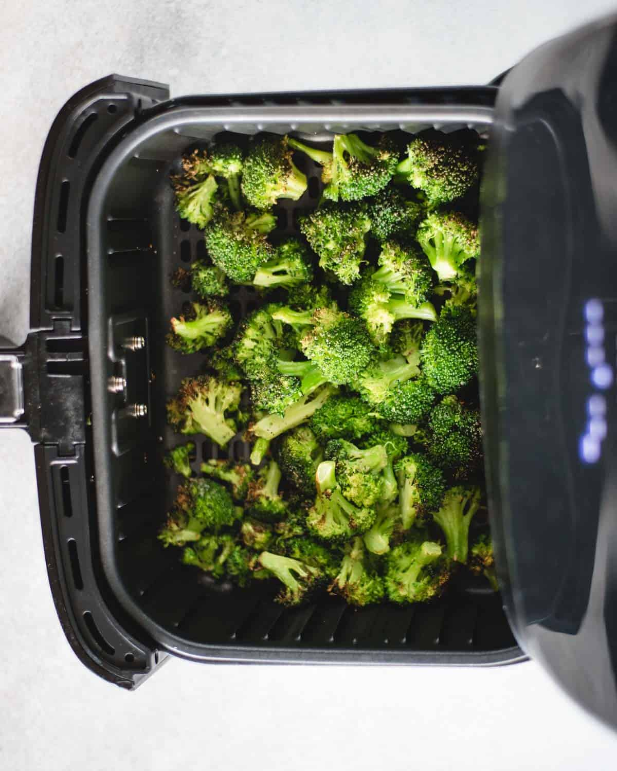 air fryer basket open showing cooked broccoli