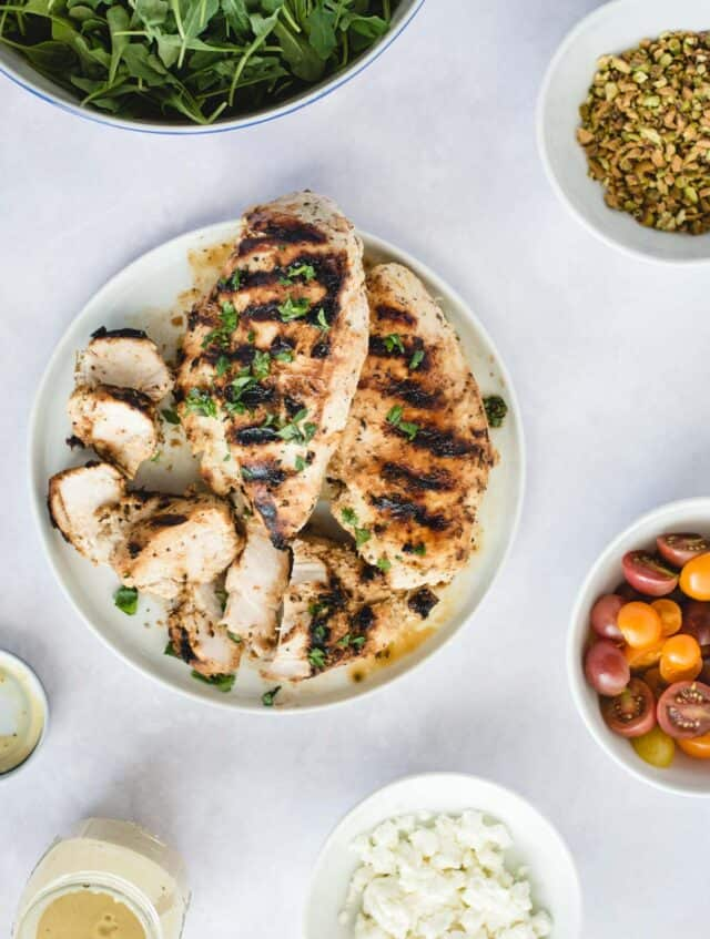 over head picture of plate with grilled chicken and other salad ingredients on a white background
