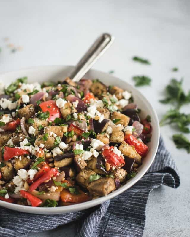 Bowl of roasted eggplant salad sprinkled with feta and herbs